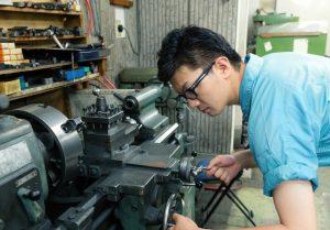 旋盤を操作する作業着男性